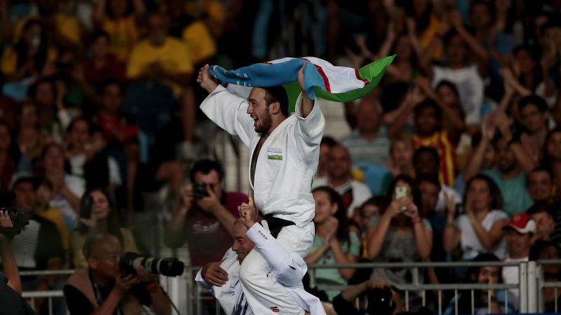 A man carrying Uzbekistan's flag on another man's shoulder