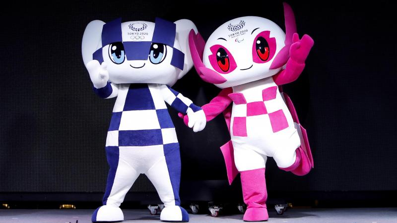 the two mascots for the Tokyo 2020 Olympic and Paralympic Games holding hands on stage