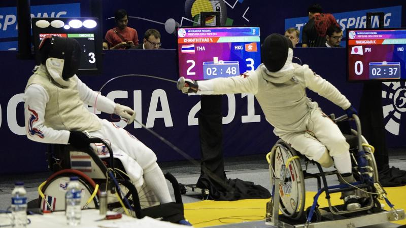 two wheelchair fencers in combat