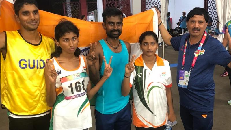 female Para athlete Rakshitha Raju standing with her guide in front of an India flag