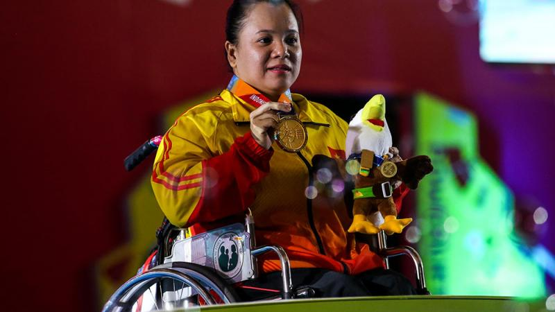 female powerlifter Dang Thi Linh Phuong on the podium holding up her gold medal