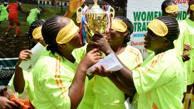 four female blind footballers kissing a trophy