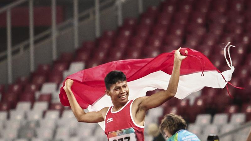 male Para athlete Sapto Yogo Purnomo running holding an Indonesia flag