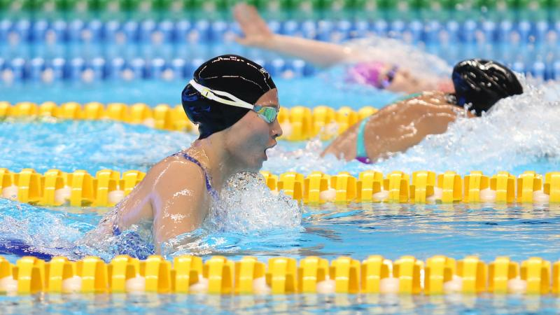 female Para swimmer Amilova Fotimakhon takes a breath during a breaststroke