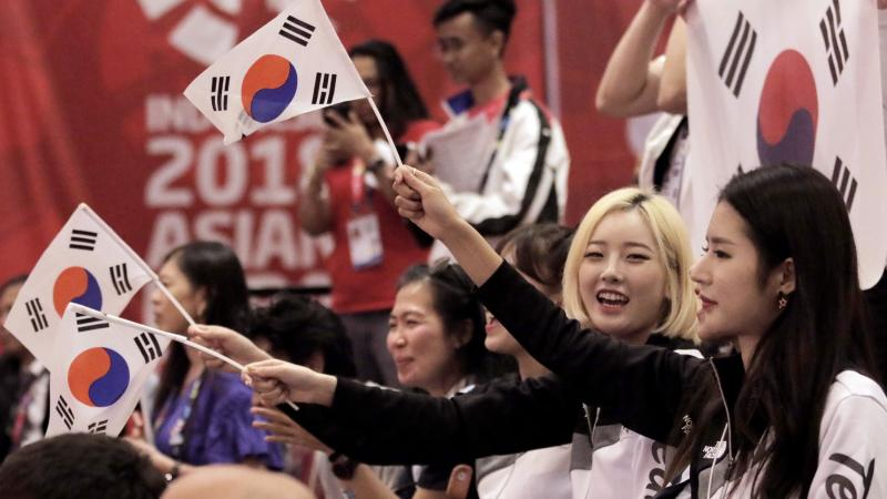 a group of men and women waving South Korean flags