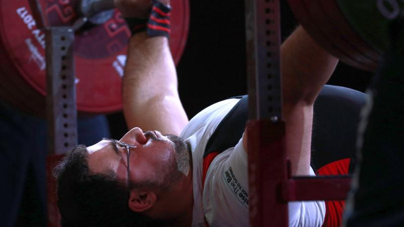 male powerlifter Roohallah Rostami gets ready to lift the bar