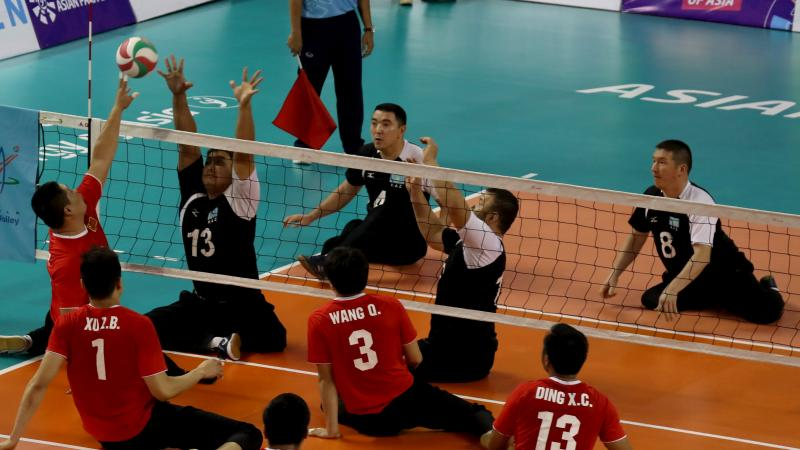male sitting volleyball players from China and Kazakhstan volleying the ball over the net