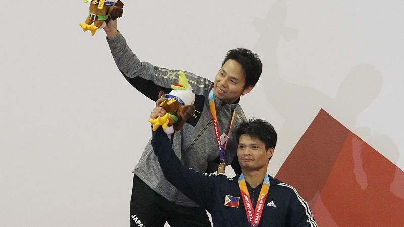 male Para swimmers Daisuke Ejima and Ernie Gawilan on the podium raising their arms