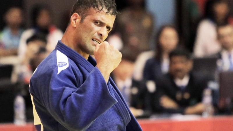 male judoka Ehsan Mousanezhad Karmozdi clenches his fist in victory