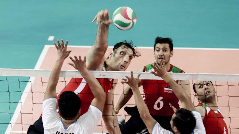 male sitting volleyball player Morteza Mehrzadselakjani blocks a ball over the net