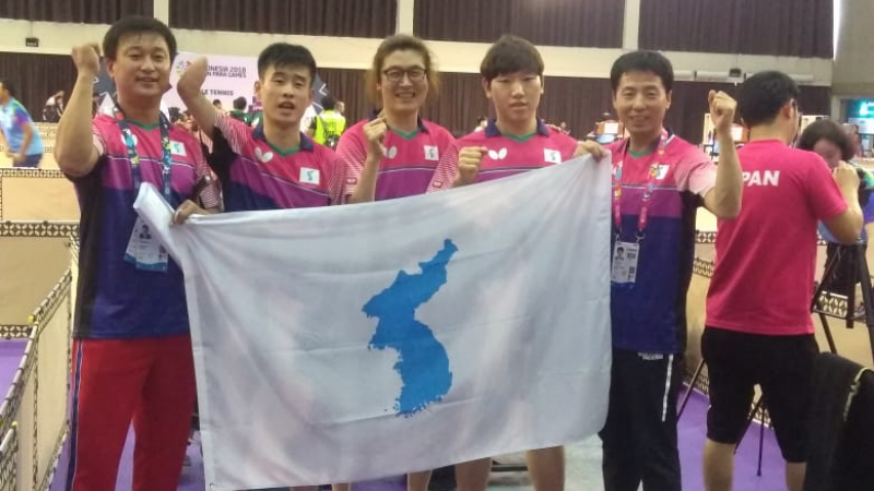 a group of Korean table tennis players standing with a United Korea flag
