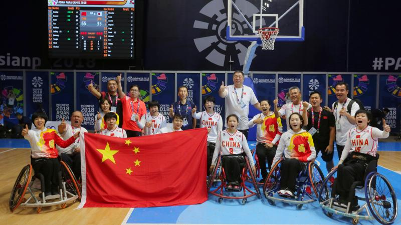 a female Chinese wheelchair basketballer shields the ball from another player