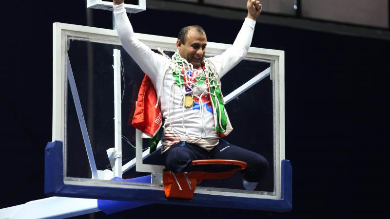 male wheelchair basketball player Morteza Ebrahimi sitting on top of the basketball hoop raising his arms
