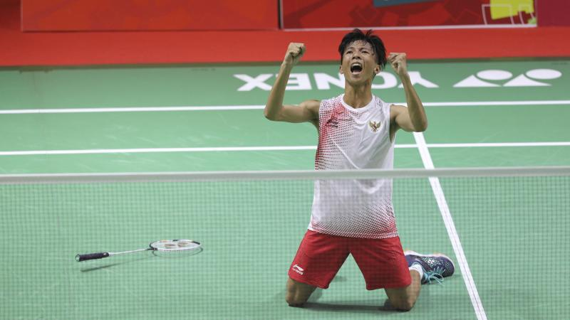 male Para badminton player Dheva Anrimusthi falls to his knees and clenches his fists on the court