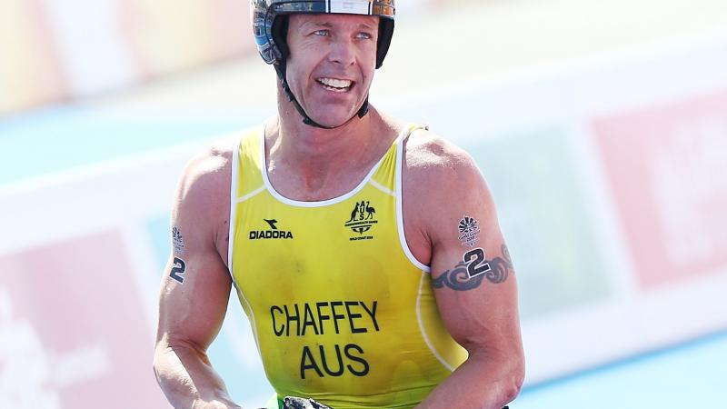 male Para triathlete Bill Chaffey smiles after crossing the finish line in his wheelchair