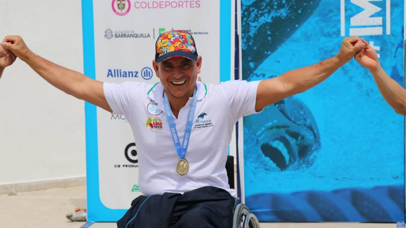 Colombian swimmer Moisés Fuentes smiling on the podium