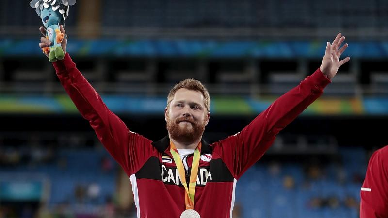 male Para athlete Alister McQueen raises his arms on the podium