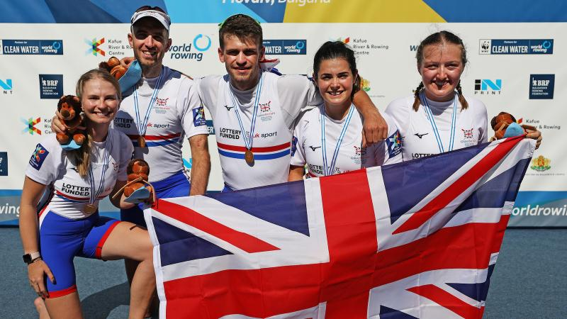 five Para rowers with Ellen Buttrick on the right holding up a Great Britain flag
