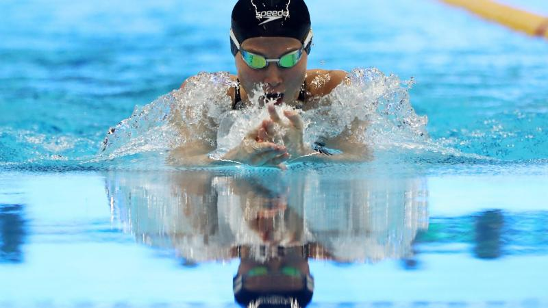 female Para swimmer Amilova Fatimakhon takes a breath during a breaststroke