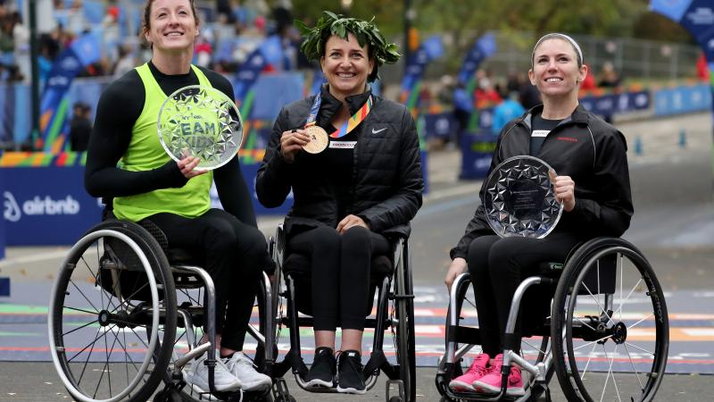 female wheelchair racers Tatyana McFadden, Manuela Schaer and Amanda McGrory holding up trophies