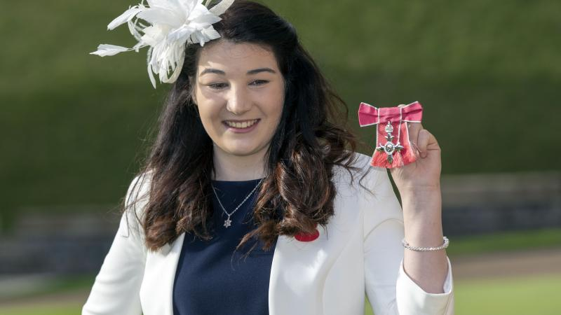 Female Para alpine skier Menna Fitzpatrick holding up her MBE medal