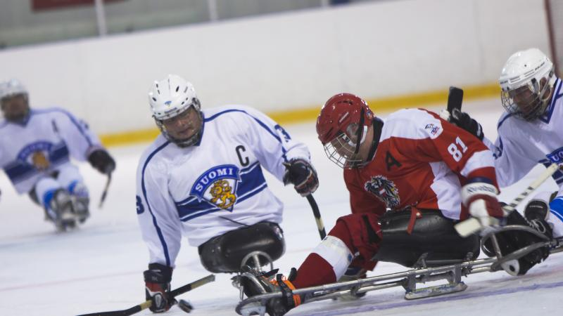 male Para ice hockey player Markku Hirvela defends the puck from a Polish player