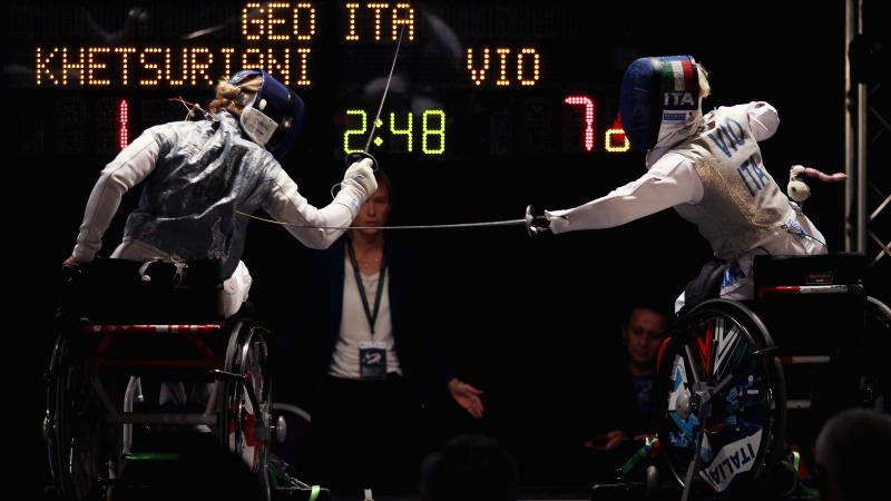 Two female wheelchair fencers competing