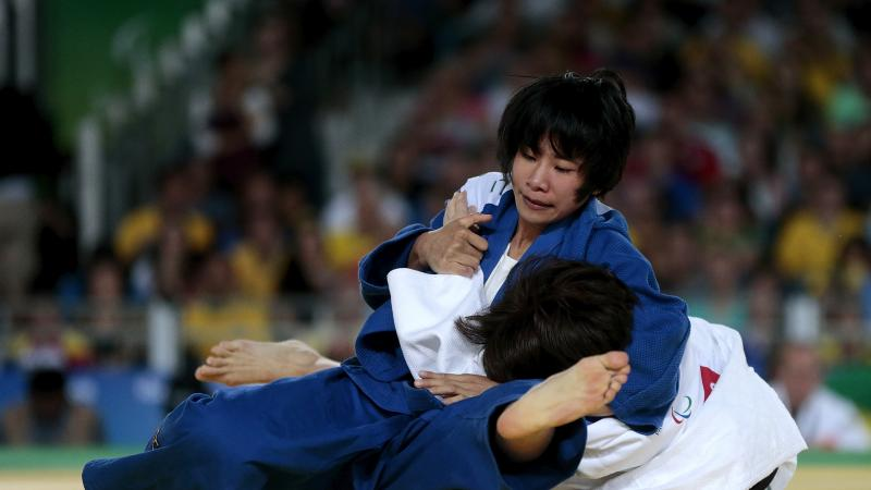 female judoka Li Liqing wrestles another female judoka to the ground on the mat