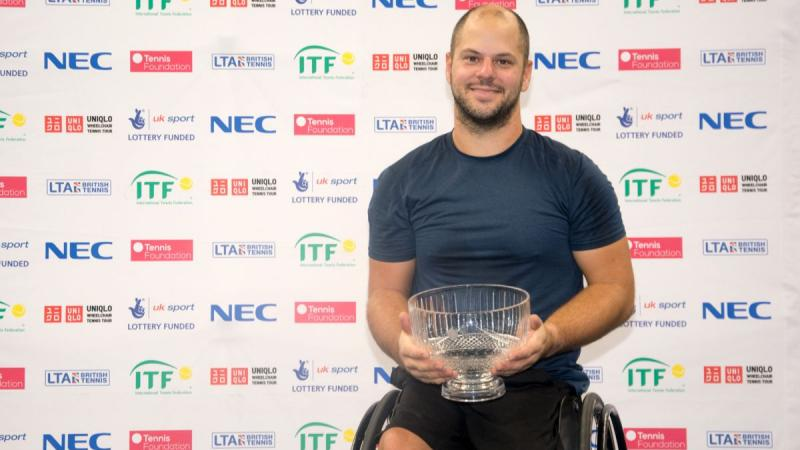 male wheelchair tennis player Stefan Olsson smiling and holding a crystal trophy