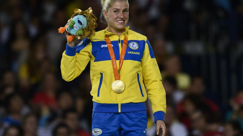 female judoka Inna Cherniak holds up a mascot teddy and her medal on the podium
