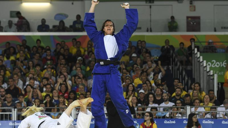 female judoka Naomi Soazo raises her arms straight up in the air in celebration
