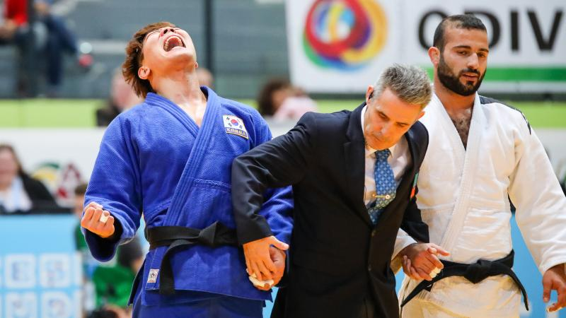 A men in suit holding the hands of two men in judo kimonos