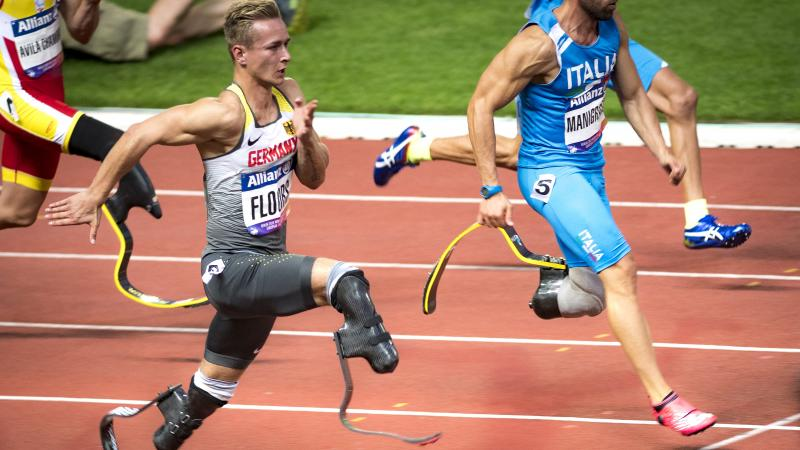 A man with prosthetic legs running against three competitors on an athletics' track
