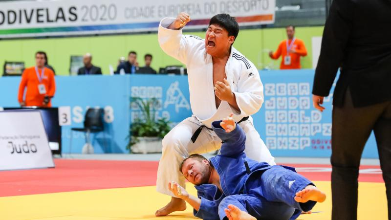 A man in a white kimono celebrates while other man in blue kimono lies on the mat