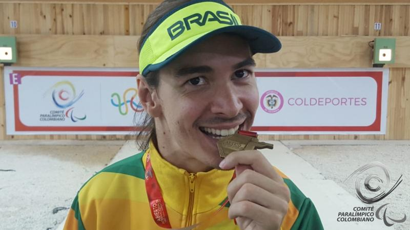 Brazilian male shooting Para sport athlete bites his gold medal