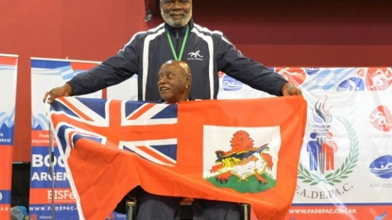 male boccia athlete Steve Wilson on the podium holding up a Bermuda flag