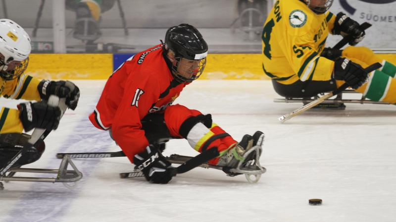 A man in a sledge playing Para ice hockey