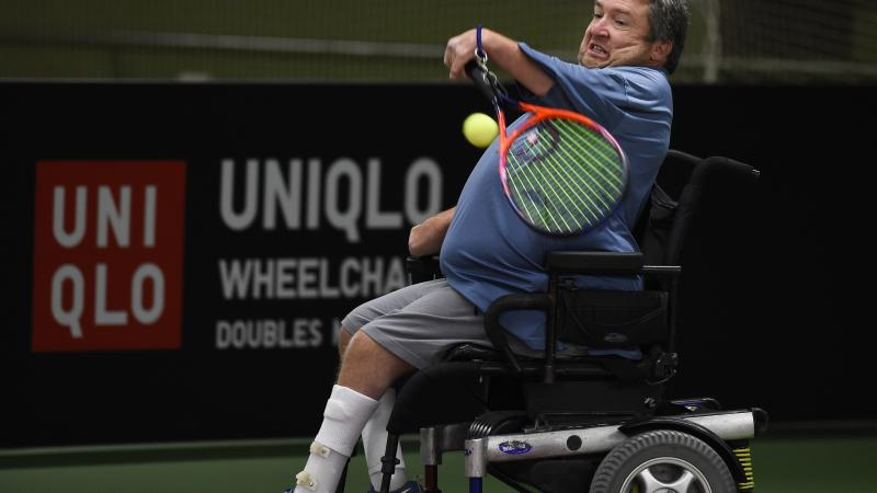 male wheelchair tennis player Nick Taylor plays a forehand on a hard court