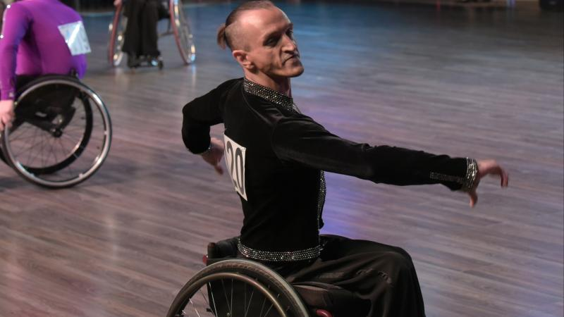 male Para dancer Ivan Sivak raises his arms in a wheelchair