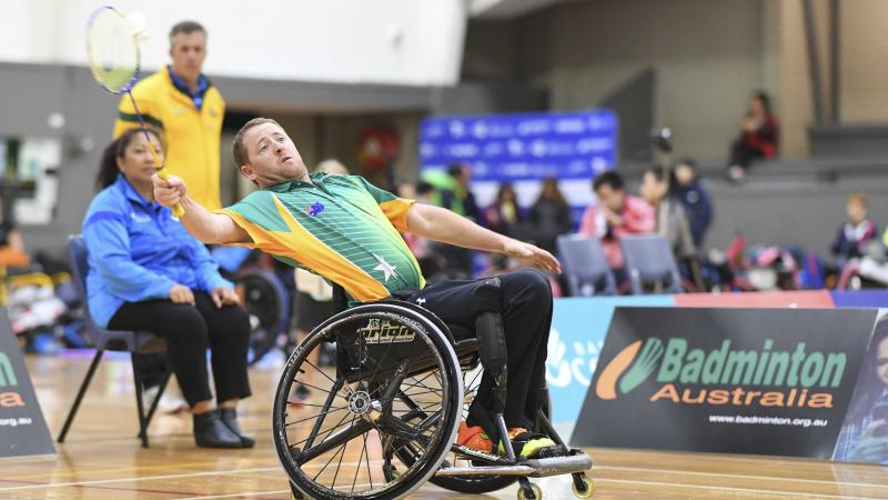Male Australian badminton player in a wheelchair attempts to hit the birdie in the air