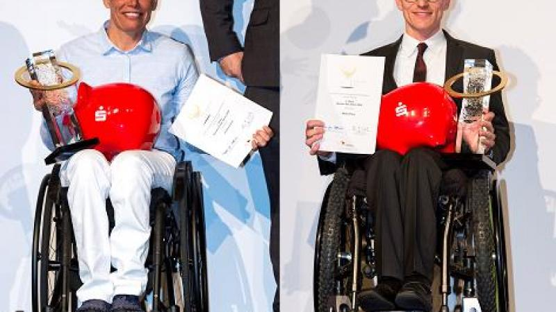 A woman and a man in wheelchairs holding a trophy and a certificate