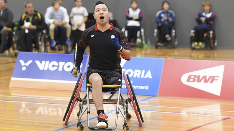 male Para badminton player Chan Ho Yuen punches the air after a winning shot