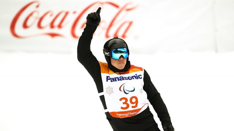 male Para snowboarder Matti Suur-Hamari raises his finger as he crosses the finish line