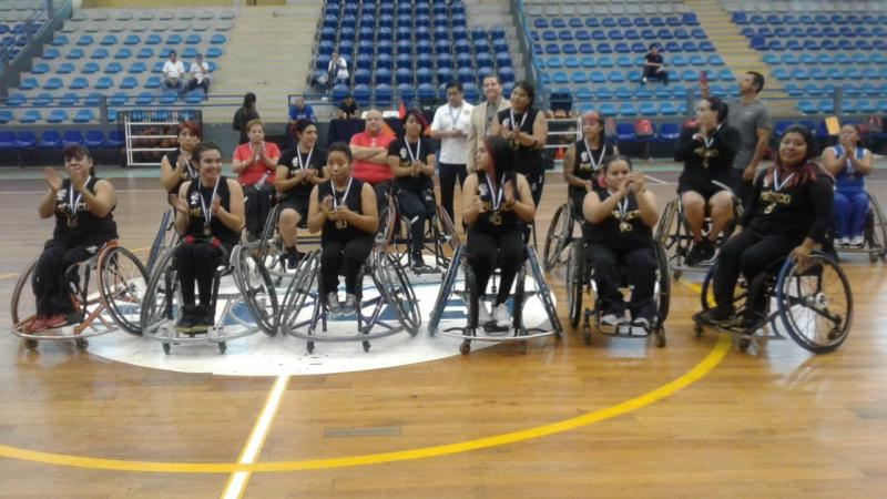 Female Mexican wheelchair basketball players pose after a victory