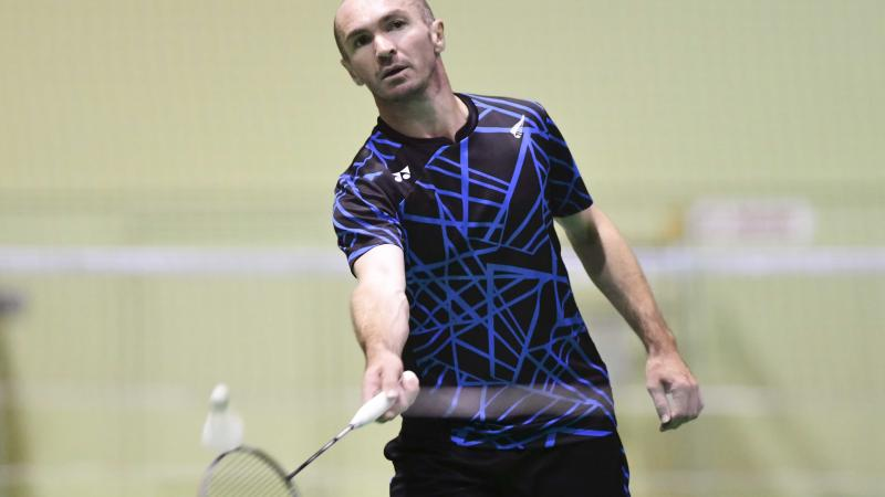 male Para badminton player Corrie Keith Robinson standing and playing a forehand shot