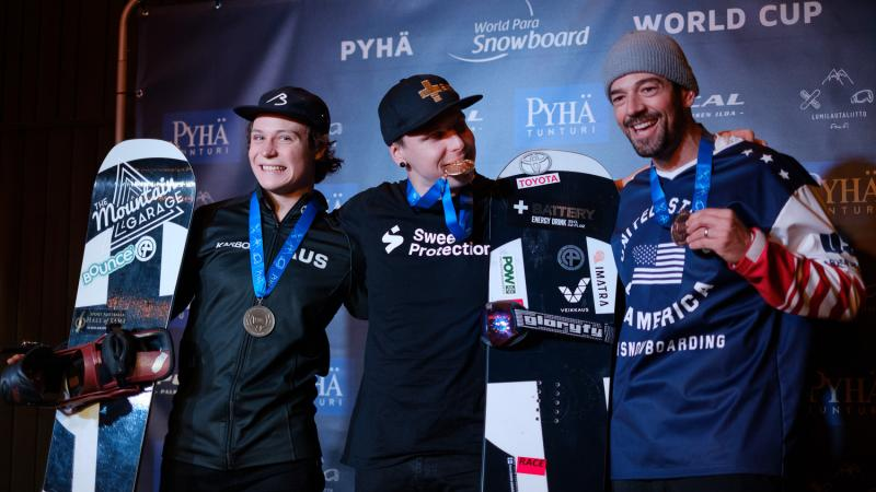 Three male snowboarders pose together with their medals