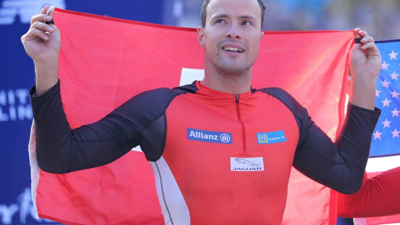 male wheelchair racer Marcel Hug holding up a Switzerland flag