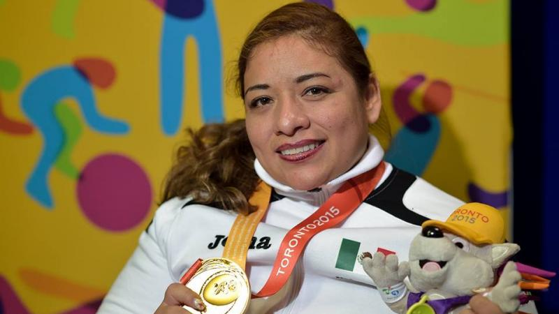 female powerlifter Amalia Perez holds up a gold medal and a toy mascot