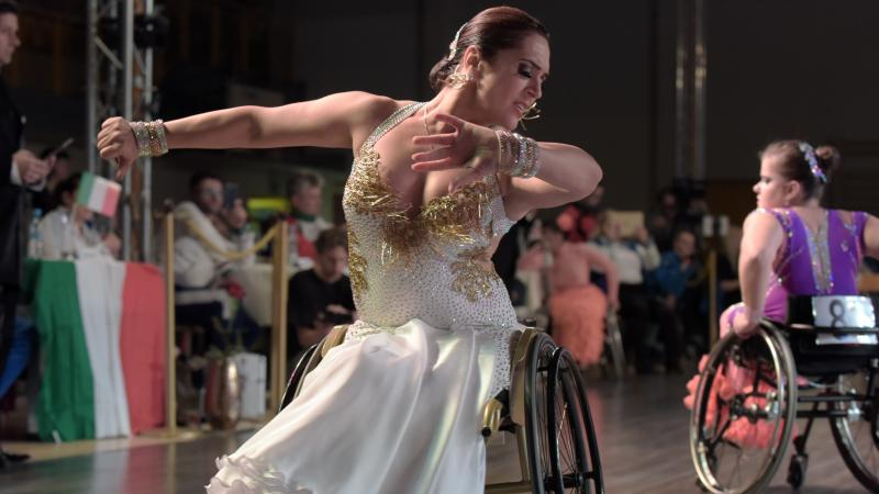 Ukrainian dancer in wheelchair wears glittering dress dances a conventional style