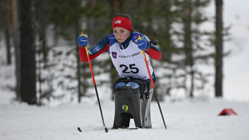 female Para Nordic sit skier Kendall Gretsch pushing through the snow
